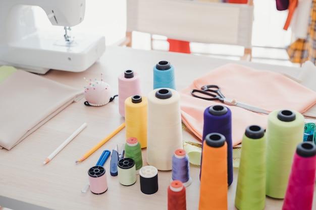 На столе дизайнера есть много аксессуаров, используемых для шитья.