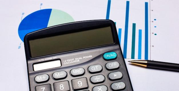 На рабочем столе калькулятор, ручка, разноцветные диаграммы.