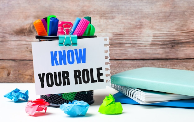 На рабочем столе и на фоне деревянной стены стоит подставка с разноцветными фломастерами, яркими бумажками и листом бумаги с текстом kow your role.