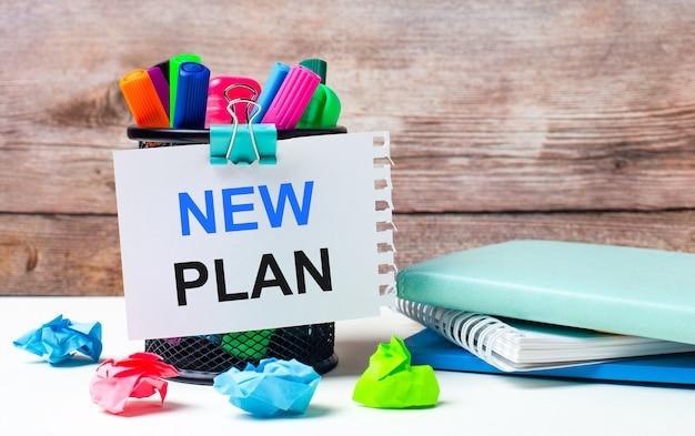 На рабочем столе и на фоне деревянной стены стоит подставка с разноцветными фломастерами, яркими бумажками и листом бумаги с текстом new plan.