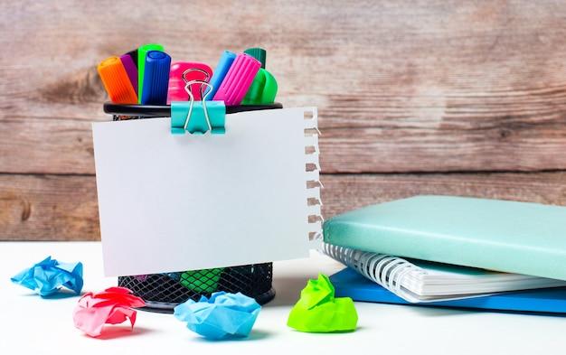 デスクトップと木製の壁を背景に、色とりどりのフェルトペン、明るい紙、テキストを挿入する場所のある一枚の紙が置かれたスタンドがあります。テンプレート