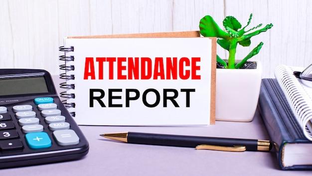 デスクトップには、電卓、日記、鉢植えの植物、ペン、および「出席レポート」というテキストが記載されたノートがあります。ビジネスコンセプト。職場のクローズアップ