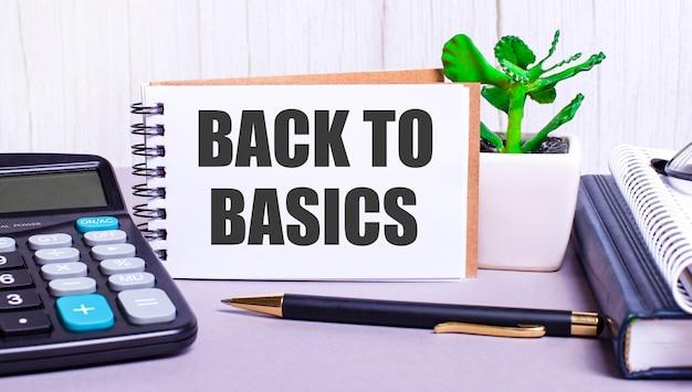 デスクトップには、電卓、日記、鉢植えの植物、ペン、そして「基本に戻る」というテキストが書かれたノートがあります。ビジネスコンセプト。職場のクローズアップ