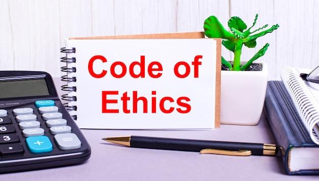 デスクトップには、電卓、日記、鉢植えの植物、ペン、および倫理規定のテキストが記載されたノートがあります。ビジネスコンセプト。職場のクローズアップ