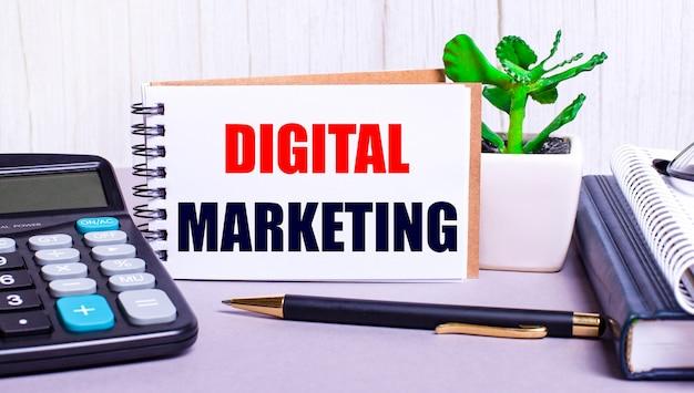デスクトップには、電卓、日記、鉢植えの植物、ペン、デジタルマーケティングというテキストのノートがあります。ビジネスコンセプト。職場のクローズアップ