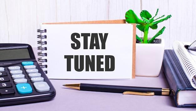 На рабочем столе калькулятор, дневники, растение в горшке, ручка и записная книжка с надписью stay tuned. бизнес-концепция. на рабочем месте крупным планом