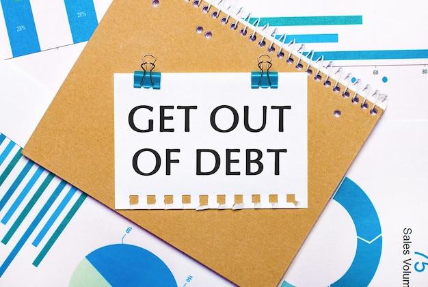 На рабочем столе синие и голубые графики и диаграммы, коричневая записная книжка и лист бумаги с синими зажимами и текстом получить долг.