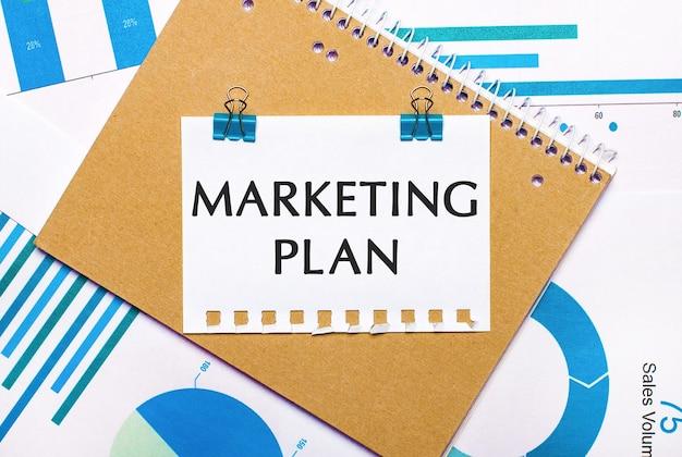 На рабочем столе синие и голубые графики и диаграммы, коричневый блокнот и лист бумаги с синими зажимами и текстом маркетингового плана.