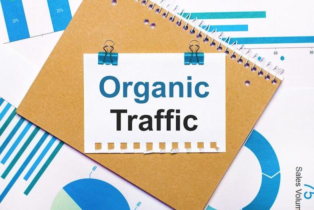 На рабочем столе синие и голубые графики и диаграммы, коричневый блокнот и лист бумаги с синими зажимами и текстом organic traffic. вид сверху. бизнес-концепция