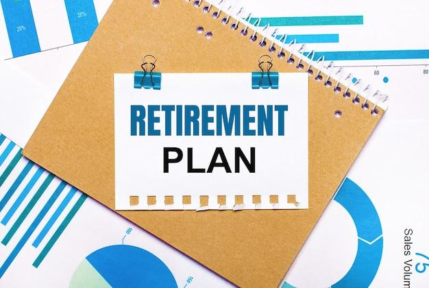 На рабочем столе синие и голубые графики и диаграммы, коричневая записная книжка и лист бумаги с синими зажимами и текстом план отпуска. вид сверху. бизнес-концепция
