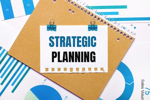 На рабочем столе синие и голубые графики и диаграммы, коричневый блокнот и лист бумаги с синими зажимами и текстом стратегического планирования. вид сверху. бизнес-концепция
