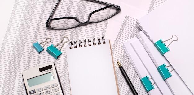 На рабочем столе очки, калькулятор, ручка и пустой блокнот с местом для вставки текста.