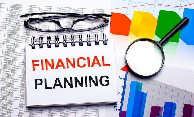 На рабочем столе очки, увеличительное стекло, цветные диаграммы и белый блокнот с текстом финансовое планирование. бизнес-концепция. вид сверху