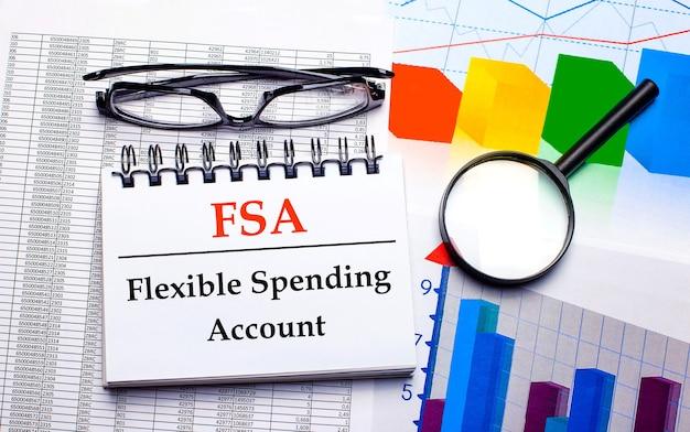На рабочем столе очки, увеличительное стекло, цветные диаграммы и белый блокнот с текстом fsa flexible spending account.