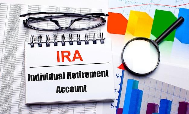 На рабочем столе - очки, увеличительное стекло, цветные диаграммы и белый блокнот с надписью «индивидуальный пенсионный счет ira». бизнес-концепция. вид сверху