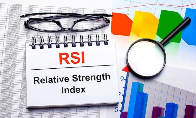 На рабочем столе находятся очки, увеличительное стекло, цветные диаграммы и белый блокнот с текстом rsi relative strength index. бизнес-концепция. вид сверху