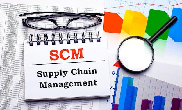 На рабочем столе очки, увеличительное стекло, цветные диаграммы и белый блокнот с текстом scm supply chain management. бизнес-концепция. вид сверху