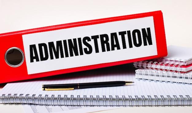 На рабочем столе блокноты, ручка и красная папка для бумаг с текстом администрация. бизнес-концепция