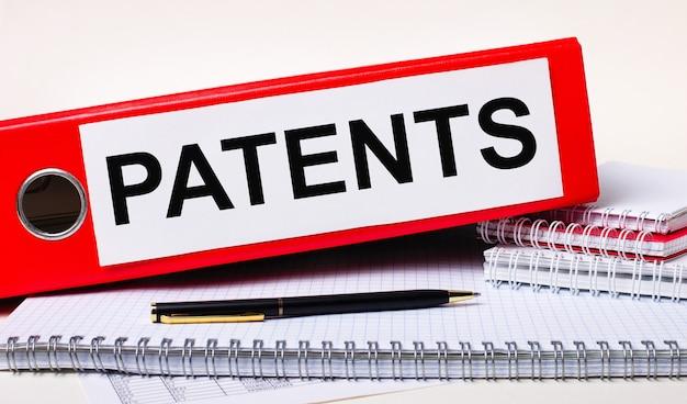 데스크탑에는 공책, 펜, 그리고 patents라는 텍스트가 있는 서류용 빨간색 폴더가 있습니다. 비즈니스 개념