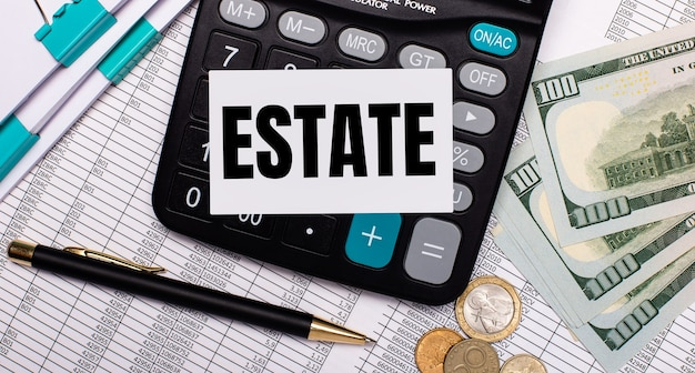 На рабочем столе отчеты, ручка, деньги, калькулятор и карточка с текстом estate. бизнес-концепция