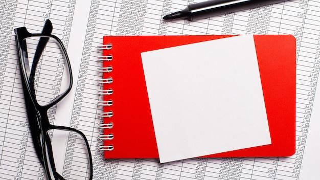 デスクトップには、レポート、赤いメモ帳、マーカー、黒いフレームのメガネ、書き込み用の白い紙があります。