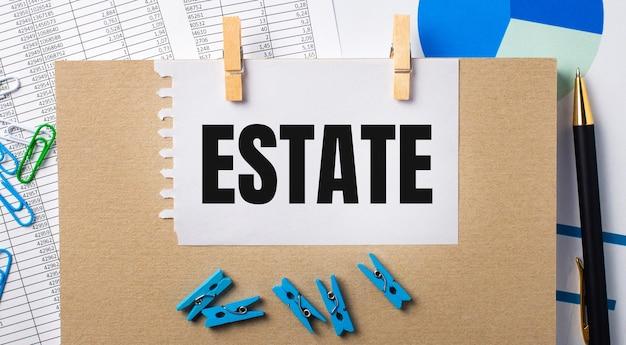 На рабочем столе отчеты, синие прищепки и диаграммы, ручка, блокнот и лист бумаги с текстом estate. бизнес-концепция