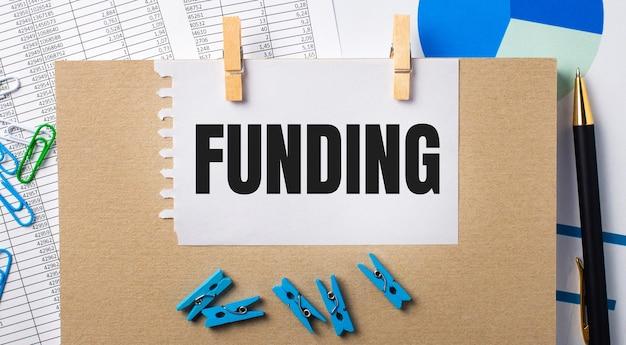 바탕 화면에는 보고서, 파란색 옷핀과 차트, 펜, 공책, funding이라는 텍스트가 적힌 종이가 있습니다. 비즈니스 개념