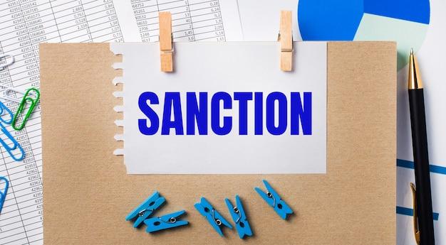 На рабочем столе отчеты, синие прищепки и схемы, ручка, блокнот и лист бумаги с текстом санкция. бизнес-концепция