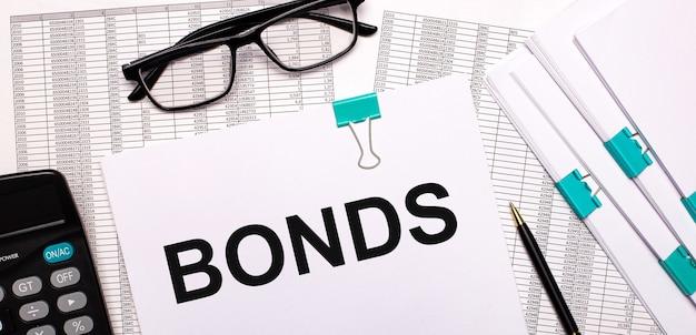 На рабочем столе отчеты, документы, очки, калькулятор, ручка и бумага с текстом bonds. бизнес-концепция