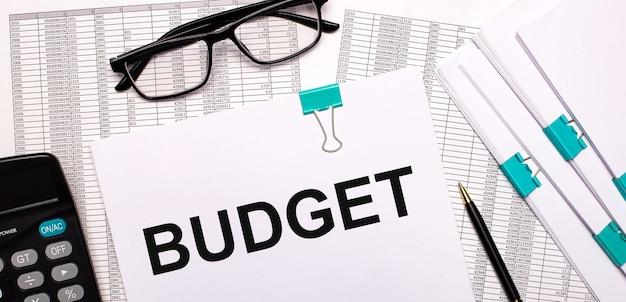 На рабочем столе отчеты, документы, очки, калькулятор, ручка и бумага с текстом бюджет. бизнес-концепция