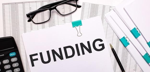 デスクトップには、レポート、ドキュメント、メガネ、電卓、ペン、紙があり、テキストはfundingです。