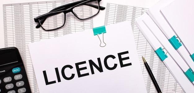 デスクトップには、レポート、ドキュメント、メガネ、電卓、ペン、紙があり、テキストはlicenceです。ビジネスコンセプト