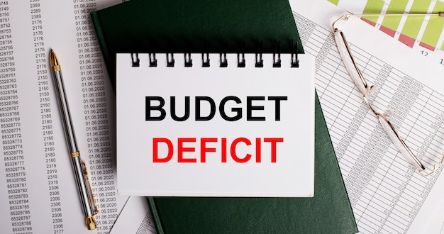 На рабочем столе отчеты, очки, ручка, зеленый дневник и белый блокнот с надписью budget deficit. крупным планом на рабочем месте. бизнес-концепция.