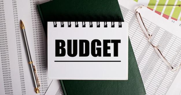 На рабочем столе отчеты, очки, ручка, зеленый дневник и белый блокнот с надписью budget. крупный план на рабочем месте. бизнес-концепция