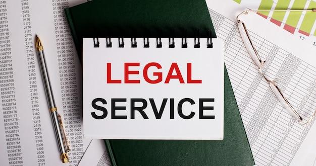 デスクトップには、レポート、メガネ、ペン、緑の日記、legalserviceという言葉が書かれた白いノートがあります。職場のクローズアップ。ビジネスコンセプト