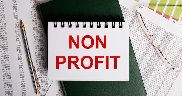 На рабочем столе отчеты, очки, ручка, зеленый дневник и белый блокнот с надписью non profit. крупный план на рабочем месте. бизнес-концепция