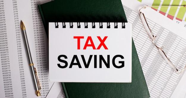 デスクトップには、レポート、メガネ、ペン、緑の日記、taxsavingという言葉が書かれた白いノートがあります。