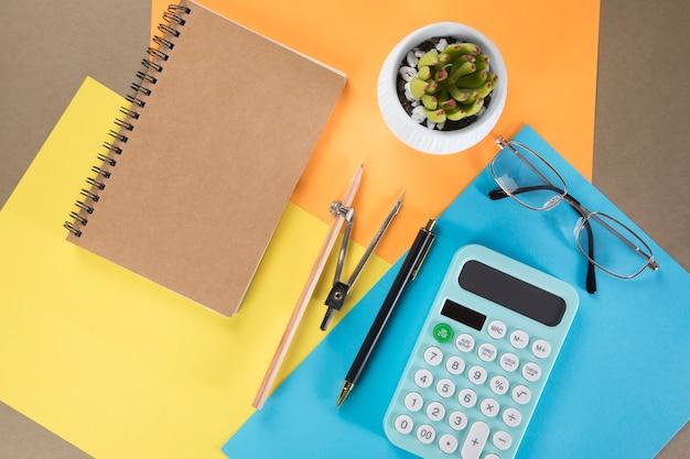デスクトップ電卓、メモ帳、ペン、キャリパー。色とりどりの紙