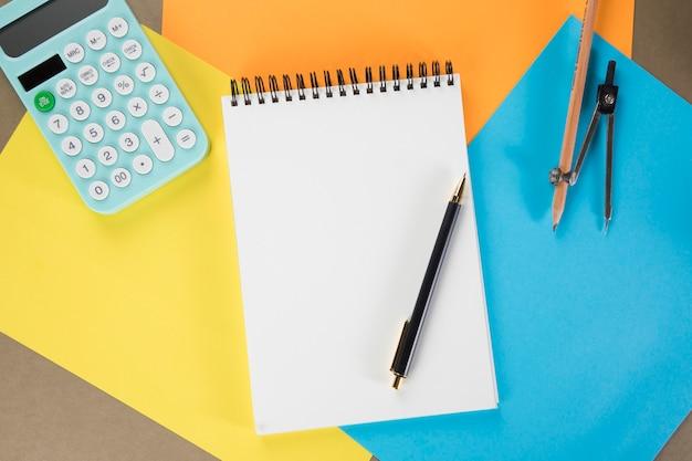 デスクトップ電卓、メモ帳、ペン、キャリパー。色とりどりの紙 Premium写真