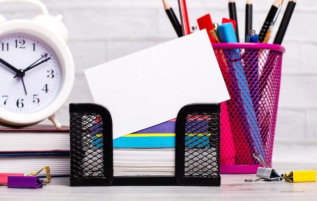 オフィスのデスクトップには、日記、目覚まし時計、文房具、テキストを挿入する場所のある白い空白のカードがあります。テンプレート。ビジネスコンセプト。