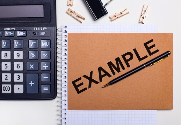 デスクトップには、電卓、ペン、洗濯バサミがノートブックの近くにあり、「example」というテキストが表示されています。ビジネスコンセプト。上から見る