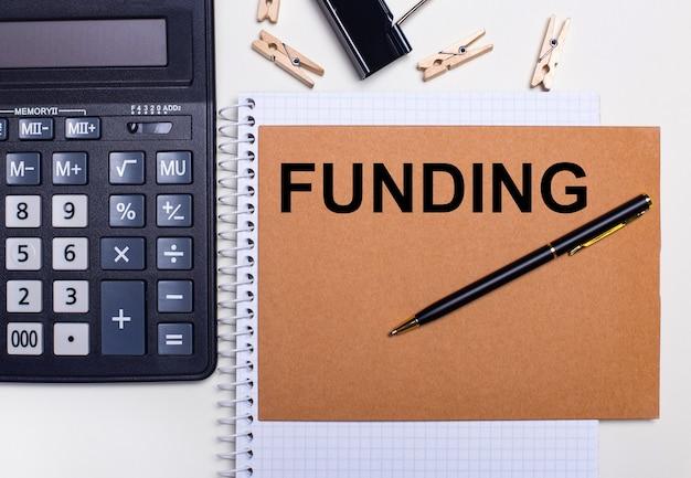 デスクトップには、電卓、ペン、洗濯バサミがノートブックの近くにあり、fundingというテキストが付いています。ビジネスコンセプト。テンプレート。上から見る
