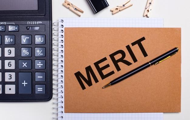 На рабочем столе калькулятор, ручка и прищепки возле записной книжки с надписью merit. бизнес-концепция. вид сверху