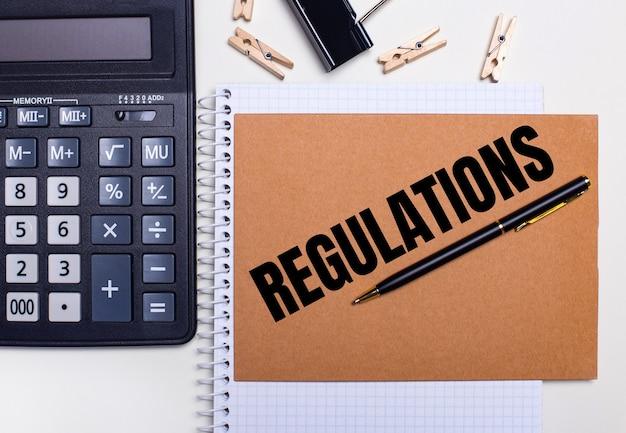 바탕 화면에는 regulations라는 텍스트가있는 노트북 근처에 계산기, 펜 및 clothespins가 있습니다.