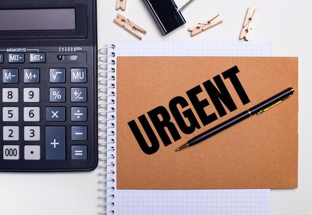 На рабочем столе калькулятор, ручка и прищепки возле блокнота с текстом срочно. бизнес-концепция. вид сверху