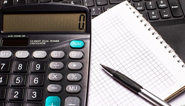 デスクトップには、コンピューターのキーボードの背景にペンと電卓が付いたノートブックがあります。ビジネスコンセプト