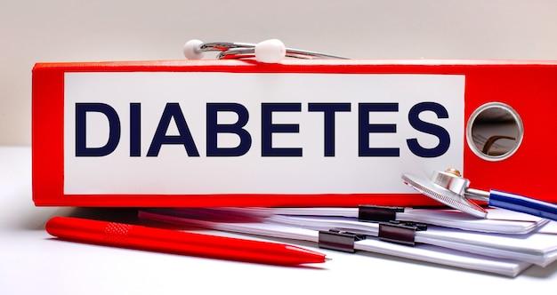 바탕 화면에는 청진기, 문서, 펜 및 diabetes라는 텍스트가 있는 빨간색 파일 폴더가 있습니다. 의료 개념
