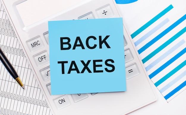 На рабочем столе белый калькулятор с синей наклейкой с текстом налоги назад, ручкой и синими отчетами. бизнес-концепция