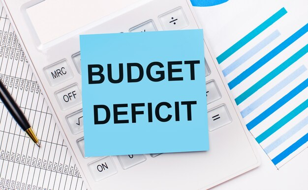 На рабочем столе белый калькулятор с синей наклейкой с текстом budget deficit, ручкой и синими отчетами. бизнес-концепция