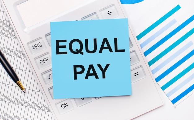 바탕 화면에는 equal pay라는 텍스트가 있는 파란색 스티커가 있는 흰색 계산기, 펜 및 파란색 보고서가 있습니다. 비즈니스 개념